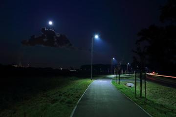 Obraz Światła samochodów w nocy i elektrownia w świetle księżyca w pełni. - fototapety do salonu