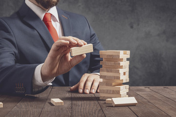 Businessman pulls out blocks from wooden tower. Conception of business strategy.