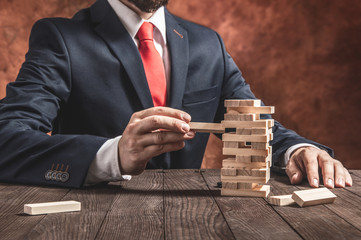 Businessman pulls out blocks from wooden tower. Conception of balance and planning in business.