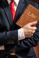 Lawyer stands with crossed hands with law book.