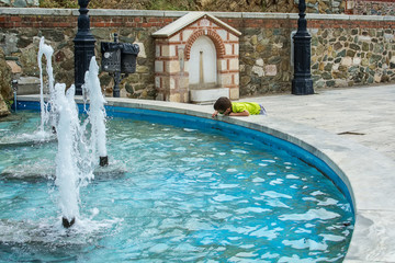 The boy is playing with water from the fountain