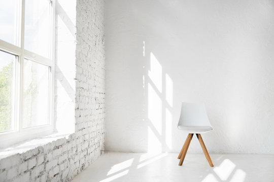 Light minimalism modern scandinavian loft studio interior with cafe furniture chair against white wall near window. Mock up shadows afternoon pattern copy space background.