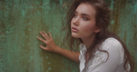 Closeup face of woman with amazing eyes. Fashion beauty portrait of girl isolated over green rusty wall background