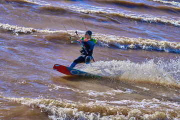 A male kiteboarder rides on a board on a large river. He performs various exercises while moving on water. Splashes of water scatter in different directions.  A sunny summer evening.