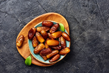 Dried dates fruits on plate with copy space. Top view of pitted dates.