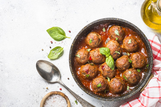 Meatballs in tomato sauce on white table.