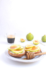 Fresh green figs sandwiches canapes Grey rustic plate Black coffee Espresso Wholegrain bread Goat cheese Healthy eating concept Appetizer Isolated Copy space White background