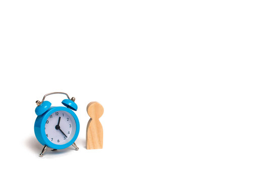 Wooden human figure stands near a blue alarm clock on a white background. The concept of hope and expectation. Queue. Planning. Business, minimalism. The passage of time, loneliness
