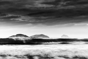 black and white seascape of distant islands lined up with crashing waves
