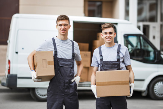 Two young handsome smiling workers wearing uniforms are standing next to the van full of boxes holding boxes in their hands. House move, mover service.