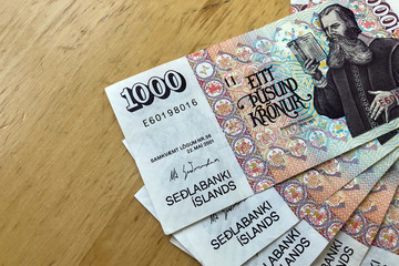 Icelandic cash. Money of Iceland. Several 1000 Icelandic krona bills on wooden table. Icelandic krona is the national currency of Iceland (kronur)
