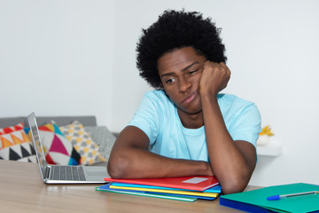 Unmotivated african american male student at desk