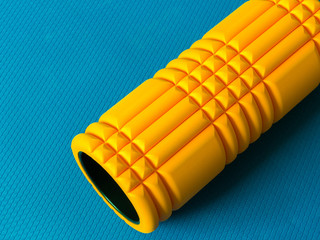 Yellow foam roller on blue background