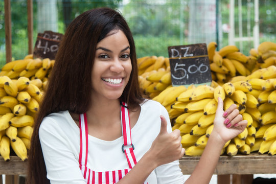 Latin american saleswoman at farmers market with bananas