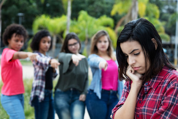 Group of girls bullying an arabic young adult woman