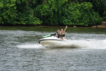 Foto op Plexiglas Water Motor sporten Happy young couple with thumbs up enjoying and having fun riding on a jet ski. Tropical coast of Sri Lanka