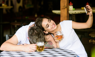 Capture shameful moment. Woman making fun of drunk friend. Girl taking selfie photo with drunk boyfriend. He appears too weak for her. Man drunk fall asleep on table and girl with full beer glass