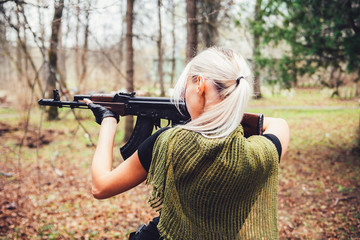 Girl with a Kalashnikov rifle in the combat zone, takes aim seeing the enemy.