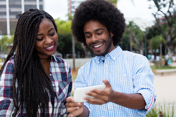 Laughing african american hipster man showing pictures at phone