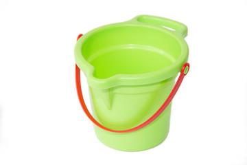 A child's green sand bucket is isolated on white background. Children's games.