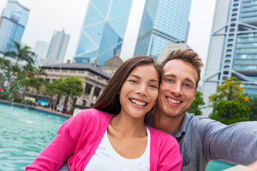 Wall Mural - Selfie tourists couple Asian woman and Caucasian taking picture with phone in Hong Kong city, Asia travel lifestyle. Two people taking a self potrait photo.