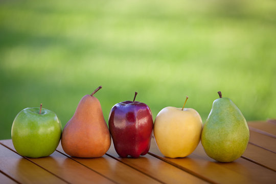 Apples and Pears lined up in a row on table