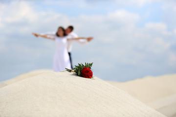 Bukiet z czerwonych róż i Młoda Para na szczycie piaszczystej wydmy.