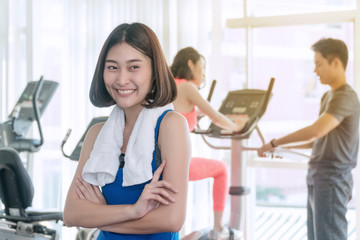 Cheerful sports woman standing arms crossed in fitness gym. Attractive woman wearing blue sportswear smiling happily at gym in front of elliptical machines.