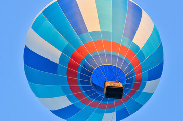 Close up of multicolored hot air balloon in blue sky. Bottom view.