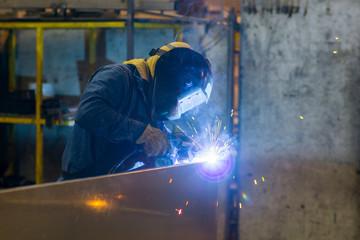 Worker soldering metal sheets