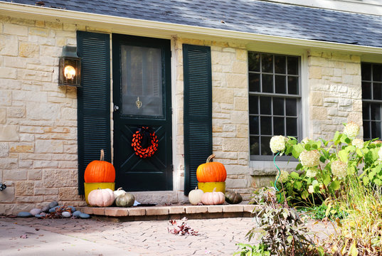 Seasonal house outdoor decoration. Main entrance stair of the brick house decorated for autumn holidays season.