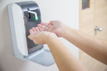 2 hands under the automatic alcohol dispenser. Infection and hospitably concept. save and clean in the public area.