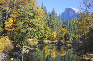 A reflection of Half Dome in the Merced River mirrors the autumn foliage changing color in Yosemite Valley National Park.
