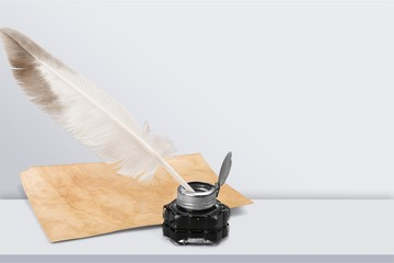 White feather quill pen, glass inkwell and
