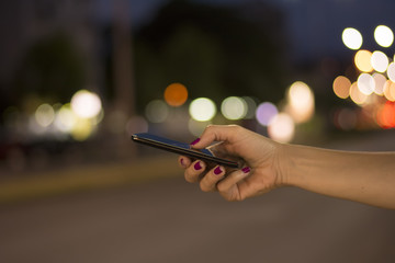 Close View of Female Hand Holding Smart Phone During Night