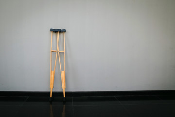 Crutches at wall.Success concept with crutches in the shadow of ladder. Insurance for heath care concept. Pair Of Two Crutches Leaning On White Wall.