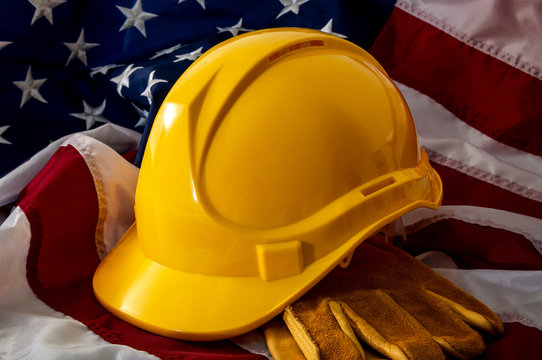 American employment in construction, Labour day and industrial work concept with close up on a yellow hard hat and safety gloves on the USA flag
