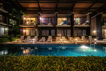 long exposure night shot image of poolside resort building with swimming pool and pool chairs along...