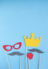 Colorful photo booth props glasses, lips, crown and moustaches on blue background with copyspace.