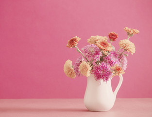 chrysanthemum flowers in white jug on pink background