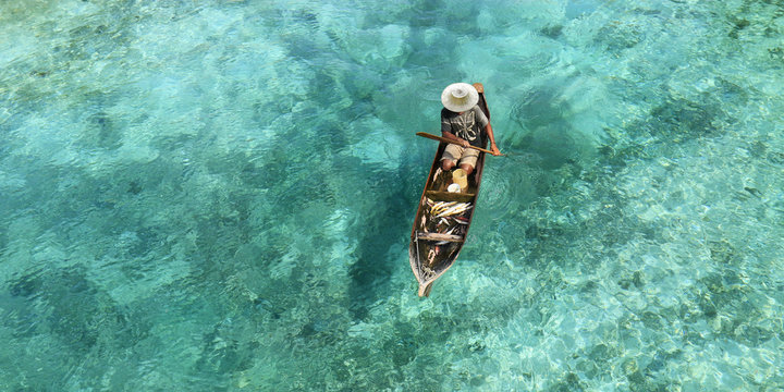 Fisherman in his boat  on turquoise sea