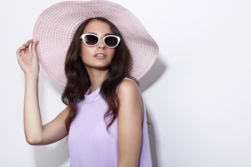 Fashion portrait of young woman wearing hat and sunglasses.