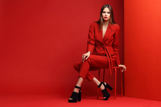 Fashion young woman in red suit.