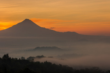 Mountain under the orange sky in the misty morning
