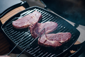 Close up shot of man cooking beef steak on a grill. Raw steak. BBQ