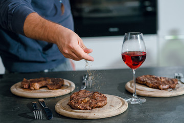 Man putting herbs and spices on the grilled well done steaks. Dinner with red wine.
