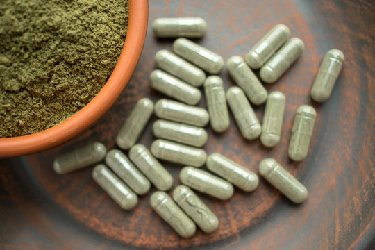 Supplement kratom green capsules and powder on brown plate. Herbal product alt-medicine kratom is  opioid. Home alternative pain remedy, opioid addiction, dangerous painkiller, overdose.