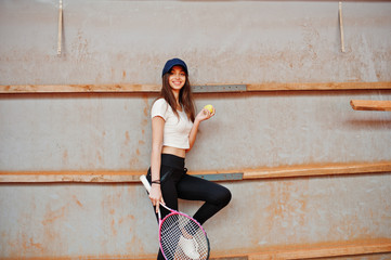 Young sporty girl player with tennis racket on tennis court.