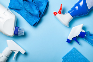 Cleaning supplies - bottles, sprays sponge on bright pastel background