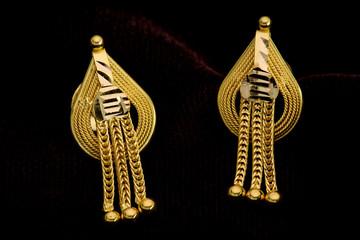 Golden earrings on a dark pattern